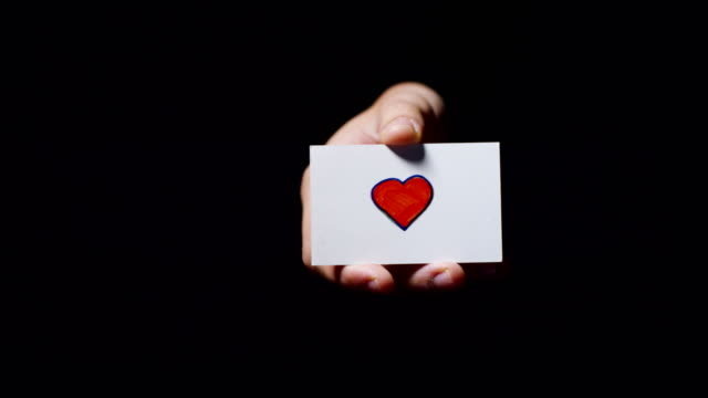 a hand showing a card with drawn a heart isolated on a black background. - повторный запуск стоковые видео и кадры b-roll