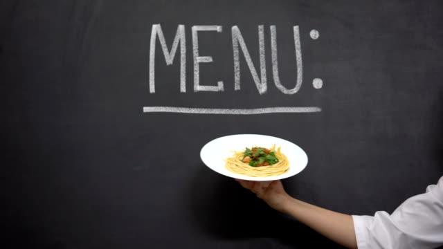 vidéos et rushes de plaque d'affichage de main avec des pâtes sur le fond de menu, délicieuses recettes de cuisson - vaisselle picto