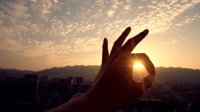ok hand sign against sunlight - znak ok filmów i materiałów b-roll