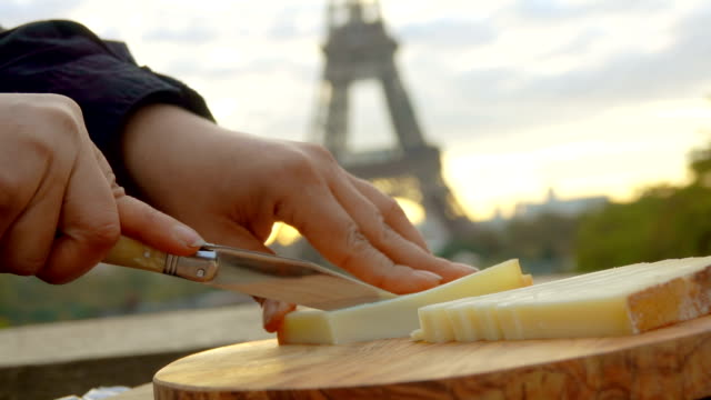 Hand slicing goat cheese on backdrop Eiffel Tower Hand slicing hard goat cheese on a wooden board with knife on the backdrop of the Eiffel Tower, Paris, France homegrown produce stock videos & royalty-free footage