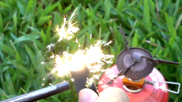 Hand sparking Magnesium fire starter to camping stove. SLO MO. video