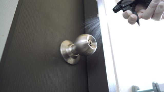 手噴灑酒精和清潔門把手在工廠的白色門,以保護冠狀病毒 - 水平面角度 個影片檔及 b 捲影像