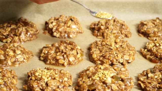 vídeos de stock e filmes b-roll de hand sprinkle flax seeds on raw oatmeal cookies 4k - oats