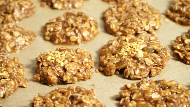 vídeos de stock e filmes b-roll de hand sprinkle flax seeds on raw oatmeal cookies. 4k - oats