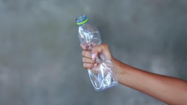 vídeos de stock e filmes b-roll de hand squash a plastic bottle - amarrotado