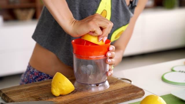 hand squeeze fresh lemon. lemon juice drains from the pulp and drips. - лимонный сок стоковые видео и кадры b-roll