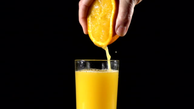 hand squeeze the orange fresh juice in glass, slow motion - сжимать стоковые видео и кадры b-roll