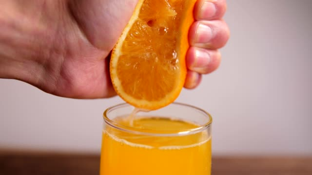 Hand squeezing fresh orange juice