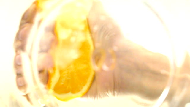 Hand squeezing fresh orange, shoot from under the glass, changing focus, slow video