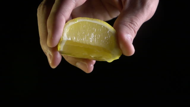 Hand squeezing lemon on black background video