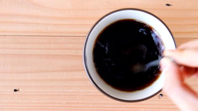 hand stir coffee on wooden background video