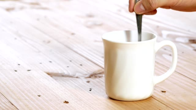 hand stirring black coffee in a white cup and picking up on wooden table man hand stirring black coffee in a white cup and picking up on wooden table mug stock videos & royalty-free footage