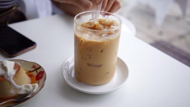 stockvideo's en b-roll-footage met hand roeren smakelijke ijskoffie. - glas serviesgoed