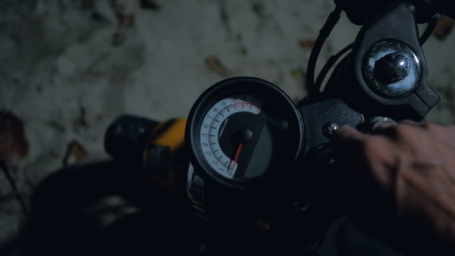 vídeos de stock e filmes b-roll de hand switches on engine of motorcycle on control board by speedometer at night - helmet motorbike