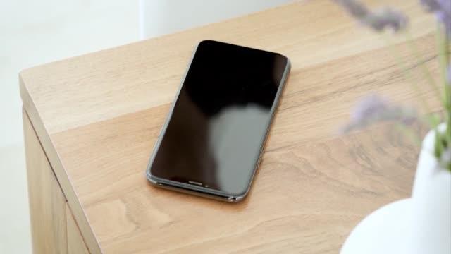 hand ta en mobiltelefon från bordet, närbild - telefonmeddelande bildbanksvideor och videomaterial från bakom kulisserna