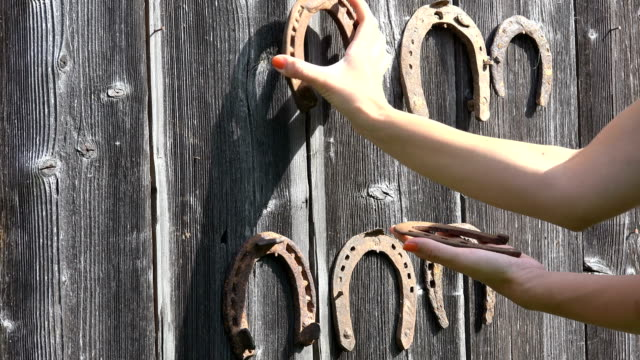 hand take off retro rusty horseshoes hanging on old wooden rural house wall. closeup. 4k - horseshoe stock videos & royalty-free footage