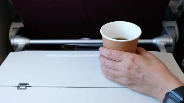 hand take out coffee cup from food tray infront of airplane seat while traveling