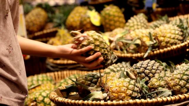 hand take pineapple in supermarket - mercato frutta donna video stock e b–roll