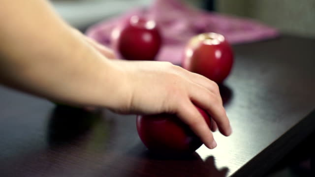Hand take red apples from wooden table. Fresh fruits. Vegetarian food video