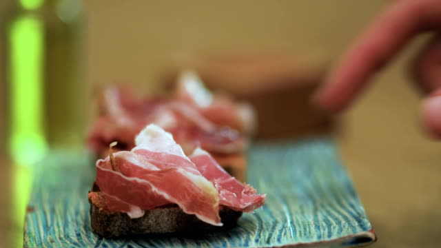 Hand takes a ham with bread tapas in a plate. Perfect Spanish tapas, traditional food in a bar or restaurant - close up