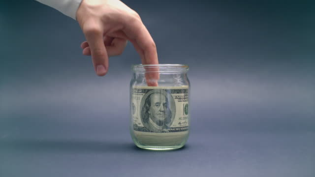 Hand Takes Money from Glass Jar video
