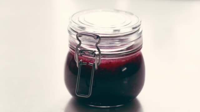 Hand taking a spoon of jam from the jar video
