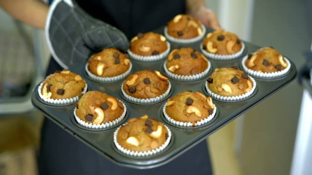 Hand taking Banana muffins tray out of oven. video