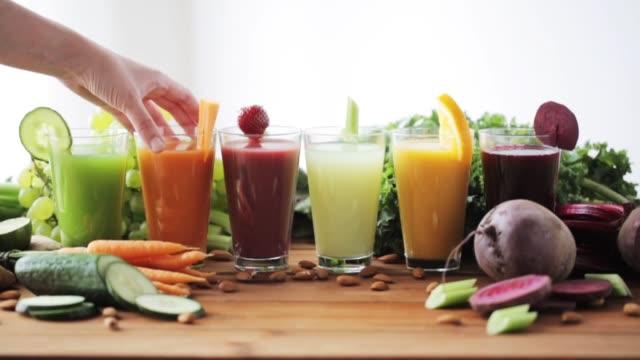 vídeos y material grabado en eventos de stock de de la mano tomando el vaso de jugo de vegetales de tabla - zumo