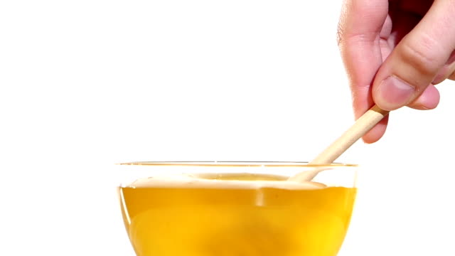 Hand taking honey from bowl using wooden spoon dipper, on white, slow motion video