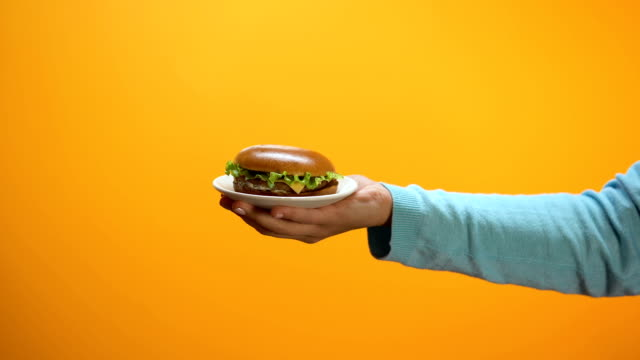 Hand taking offered tasty cheeseburger from plate on bright background, appetite