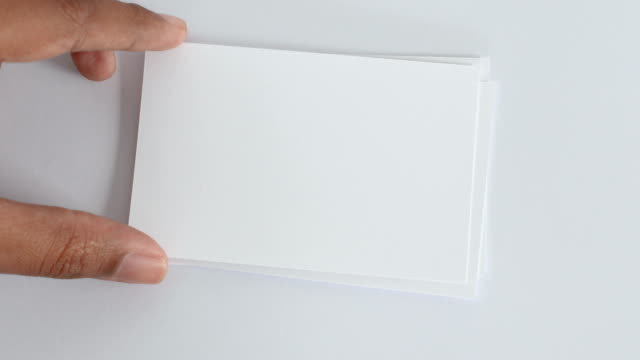 hand taking out one by one of 5 mockup empty white paper card for adding word on paper of any message concept , top view or overhead shot