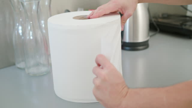 A Hand Tearing a Piece of White Paper Towel