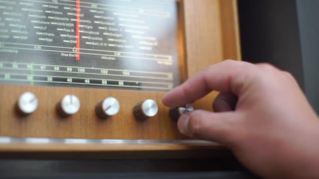 hand that twists the handle of the radio, old radio