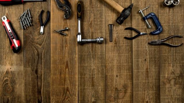 vidéos et rushes de animation d'outils de main sur la table en bois pour le logo de marque sur la feuille blanche - abaisser
