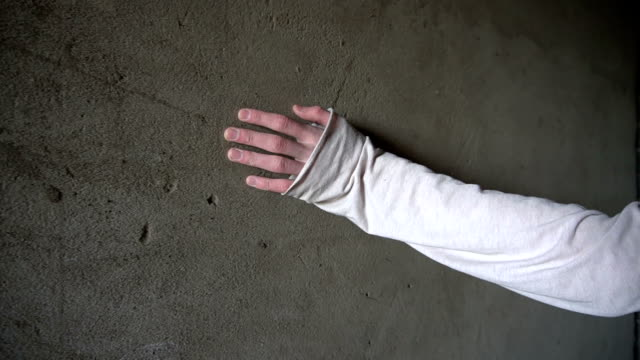 Hand touches and slides on a concrete wall with cracks video