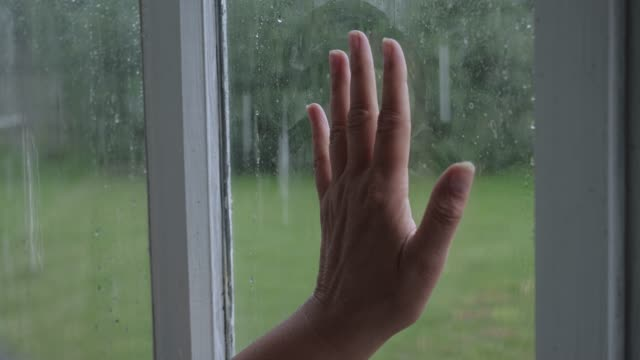hand touches window glass and slides down side behind which it is raining - hand on glass covid video stock e b–roll