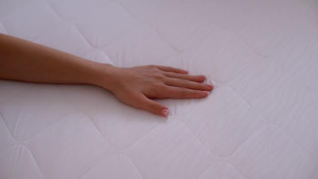 Hand touching mattress, testing elasticity and durability, quality sleep closeup