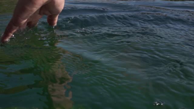 Hand touching water video