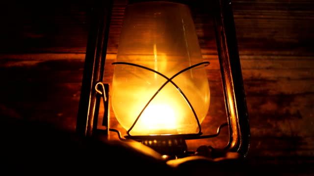 Hand turn on Lantern lamp at night