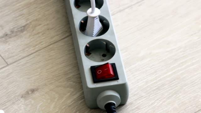 vidéos et rushes de allumer et éteindre le protecteur de surtension du bloc d'extension électrique du cordon d'alimentation. - vidéos de rallonge électrique