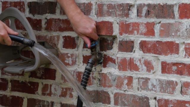 la mano accende e spegne il rubinetto dell'acqua all'aperto - tubo flessibile video stock e b–roll