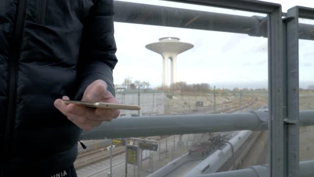 hand att skriva sms mms på en smartphone - waiting for a train sweden bildbanksvideor och videomaterial från bakom kulisserna