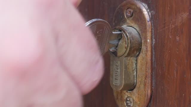 hand låsa upp med nyckel dörrlås - nyckelhål bildbanksvideor och videomaterial från bakom kulisserna