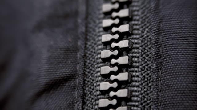 исполнение расстёгнутая молния и застежка на черной пластиковой молнией на одежде. макро - жакет стоковые видео и кадры b-roll