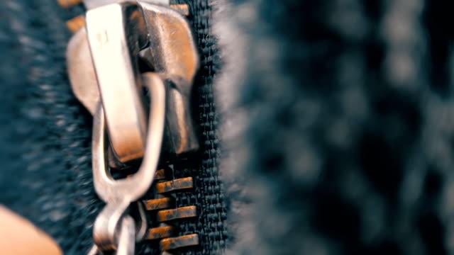 исполнение расстёгнутая молния и золотой цвета застегиваются на металлические молнии в темные одежды. макро - жакет стоковые видео и кадры b-roll