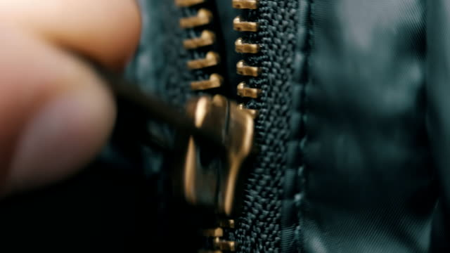 Hand unzipped and fasten golden colored metallic zipper on dark clothes. Macro video