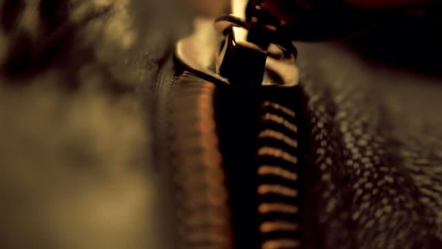 Hand unzipped and fasten golden colored metallic zipper on dark clothes. Macro video