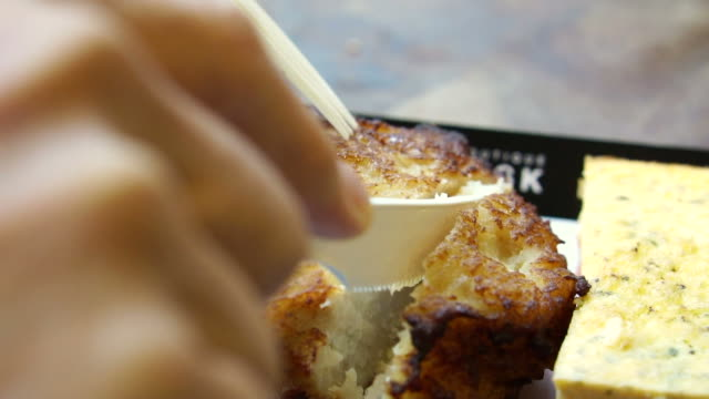 Hand use knife cutting fresh baked fish cake from European food stall video