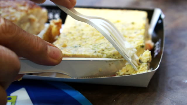 Hand use knife cutting puffy seafood omelette cake from European open market video