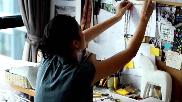 A hand using clamp to make accessories at her studio. video